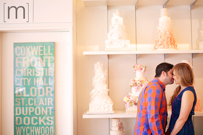 a photo of a couple kissing at the cake wall at an engagement shoot at bobbette & belle toronto
