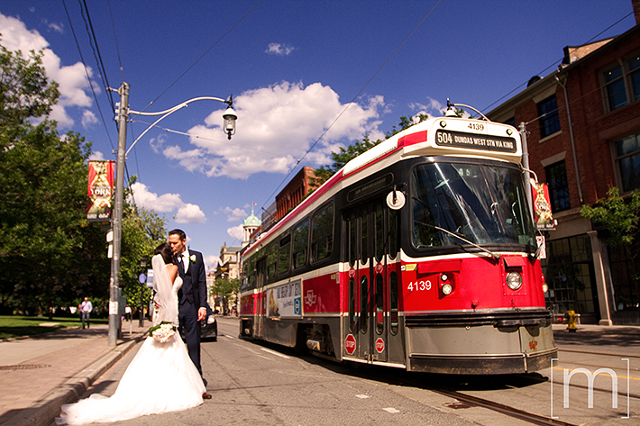 a wedding photo of the couple kissing in front of the TTC streetcar at berkeley field house toronto