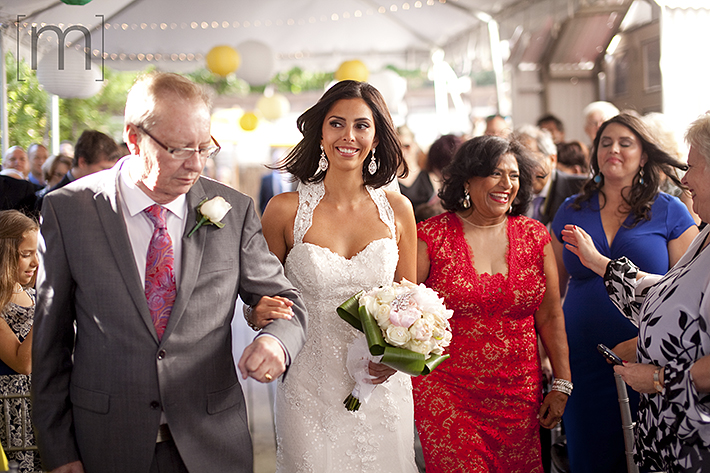 a wedding photo of the bride walking up the aisle with her parents at the ceremony at berkeley field house toronto