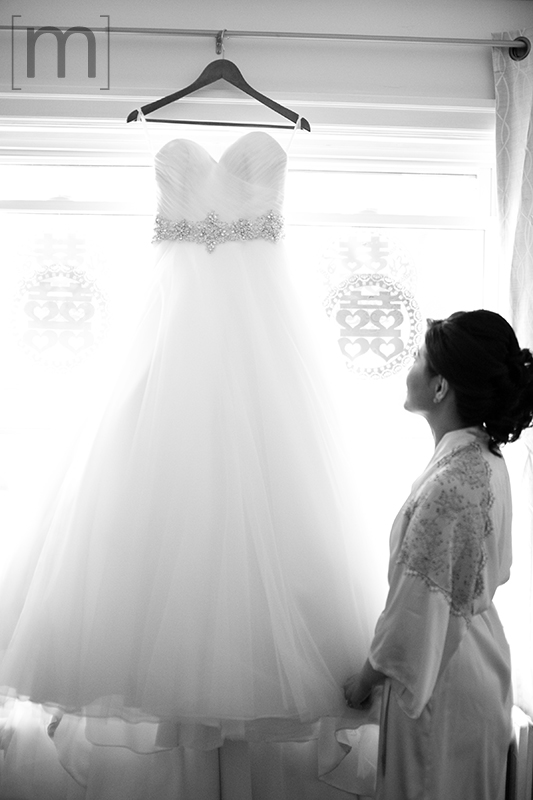 a wedding photo of the bride looking at her wedding dress at auberge du pommier toronto