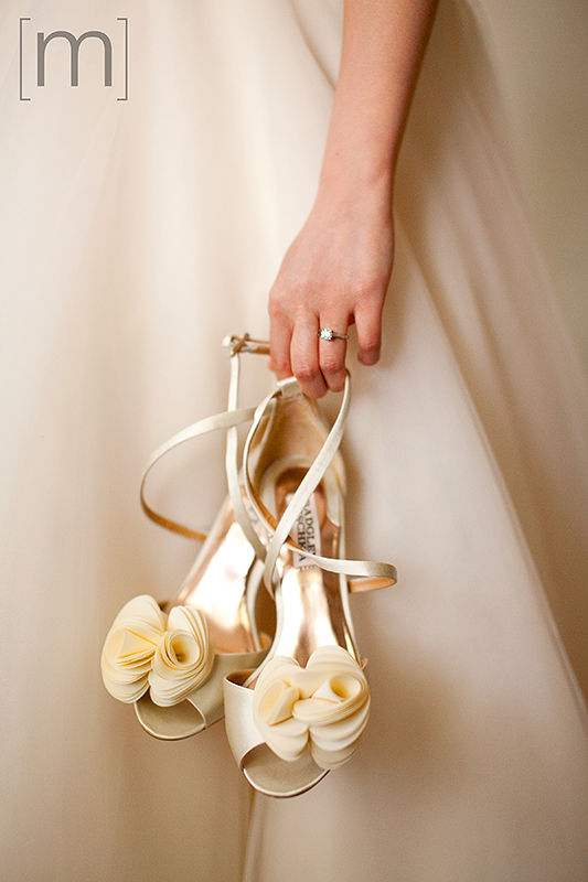 a wedding photo of the bride holding her shoes at auberge du pommier toronto