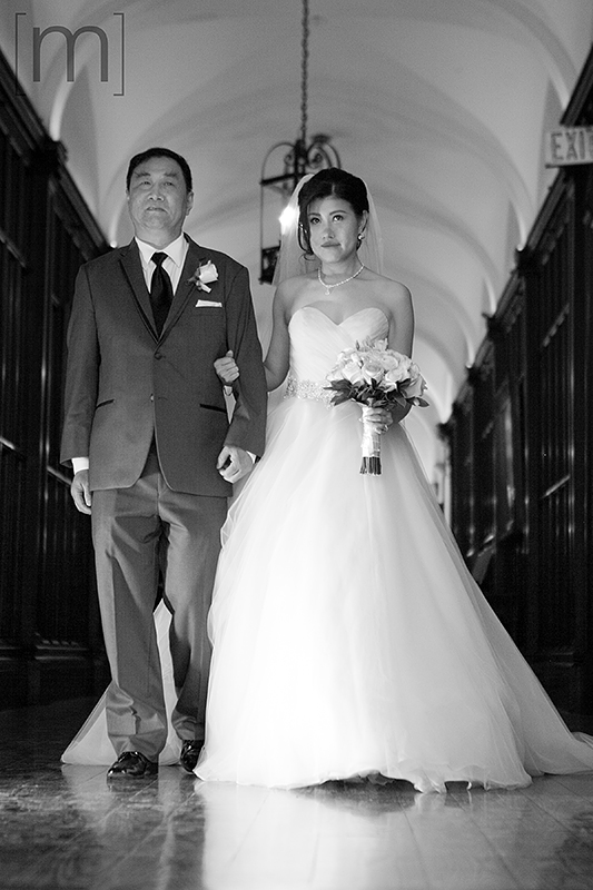 a wedding photo of the brides father walking her down the aisle at the ceremony at casa loma toronto