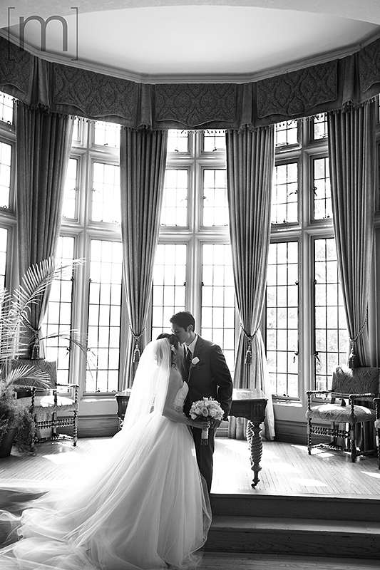a wedding photo of the bride and groom kissing at casa loma toronto