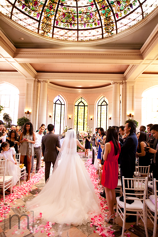 a wedding photo of the bride and groom walking down the aisle at the ceremony at casa loma toronto