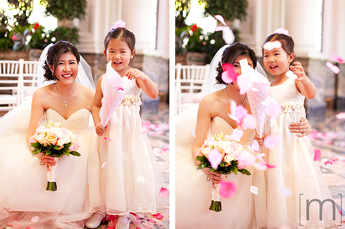 a wedding photo of the bride with flower girl and rose petals at casa loma toronto