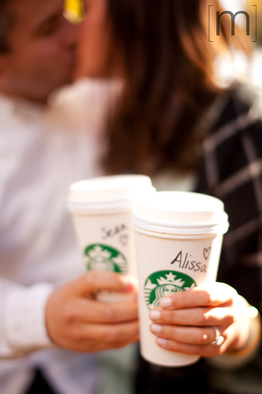a photo of a couple kissing while holding starbucks at a fall engagement at brickworks toronto