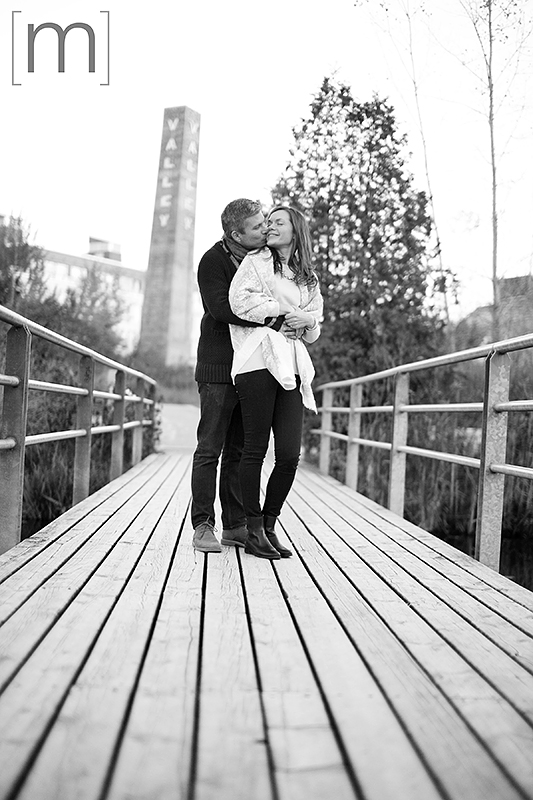 a photo of a couple cuddling on a bridge at a fall engagement at brickworks toronto black and white