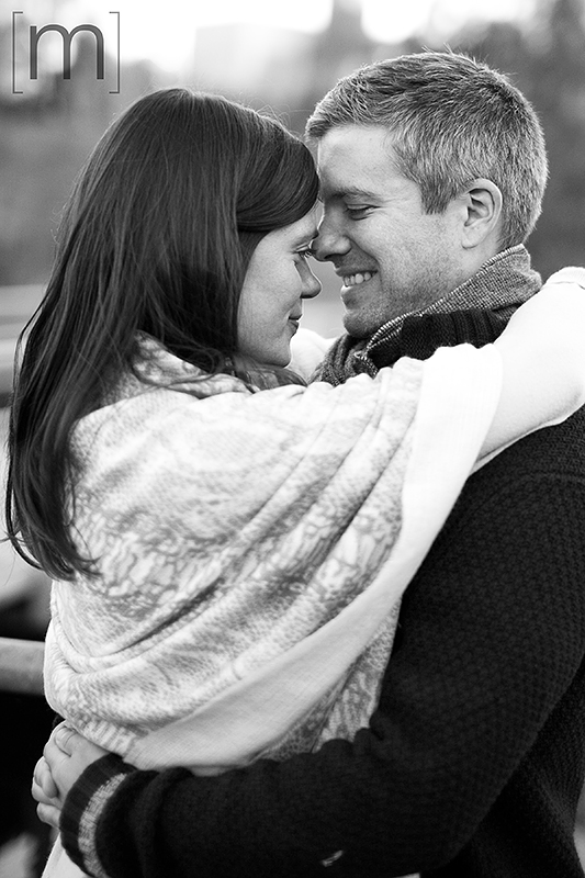 a photo of a couple smiling and holding each other at a fall engagement at brickworks toronto black and white
