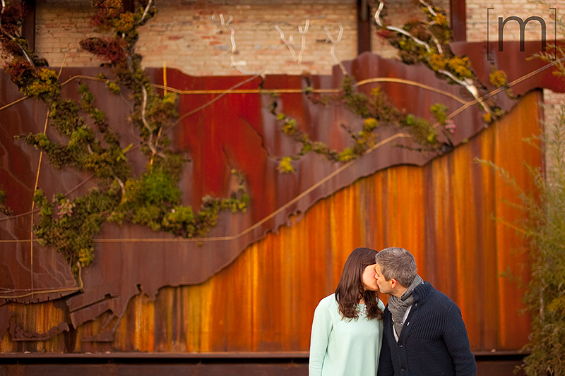 a photo of a couple kissing by the wall at a fall engagement at brickworks toronto