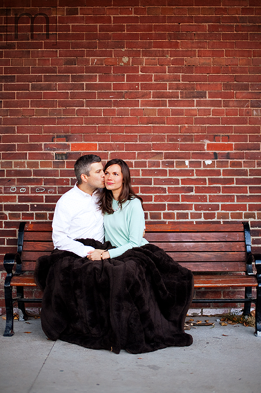 a photo of a couple cuddling on a bench at a fall engagement at brickworks toronto