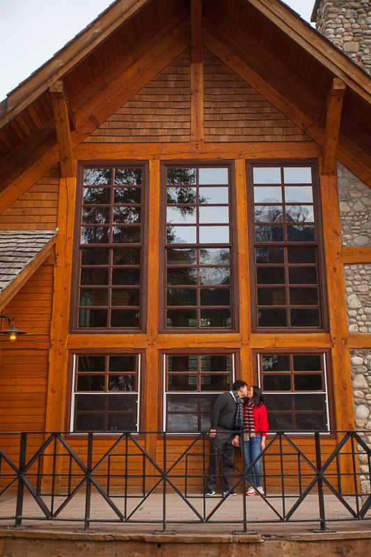 a photoshoot of a couple kissing in front of a cottage at an engagement at emerald lake at yoho park in bc