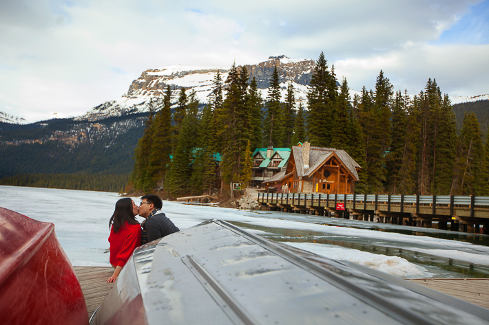 a photoshoot of a couple sitting in front of canoes at an engagement at emerald lake at yoho park in bc
