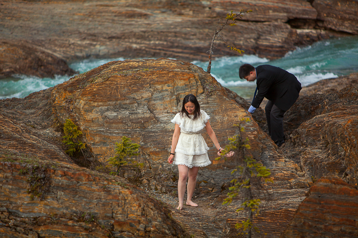 a photoshoot of a couple climbing at an engagement at emerald lake at yoho park in bc