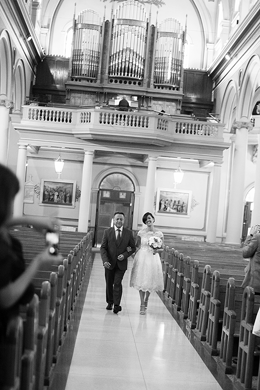 a photo of the bride and father walking down the aisle at a wedding at st pauls basilica toronto