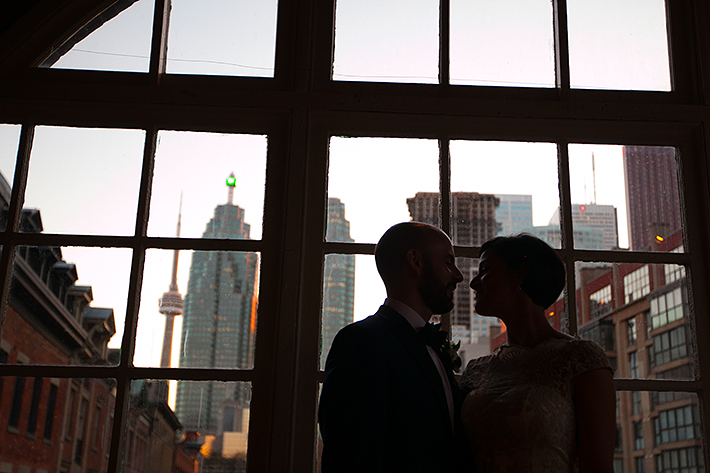 a photo of the couple silhouetted against the city at a wedding at st lawrence market toronto