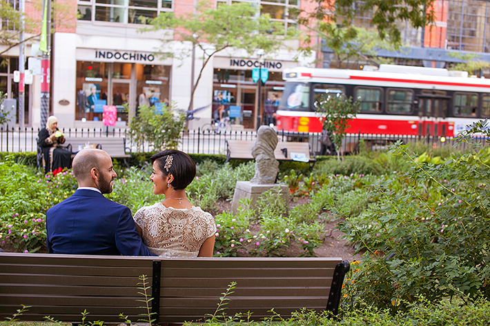 a photo of the couple sitting ttc steetcar at a wedding at st james park toronto