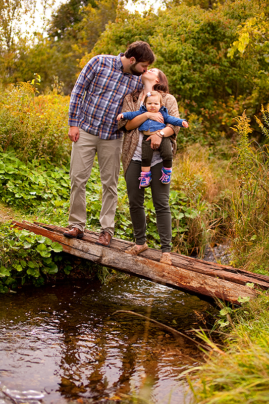 a photo of the parents holding their baby over a bridge at a fall family photography session in uxbridge ontario