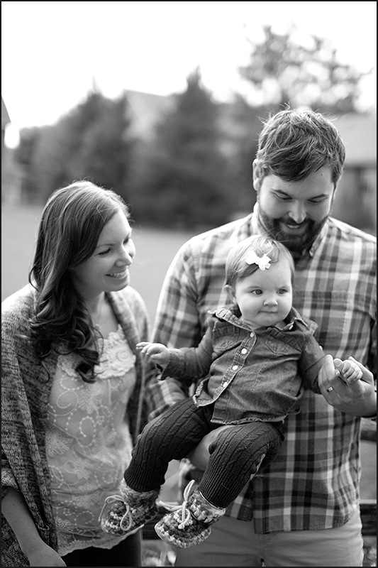 a photo of the parents holding their baby at a fall family session in uxbridge ontario