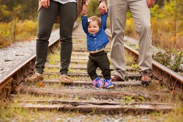 a photo of a baby walking with parents at a fall family session in uxbridge ontario