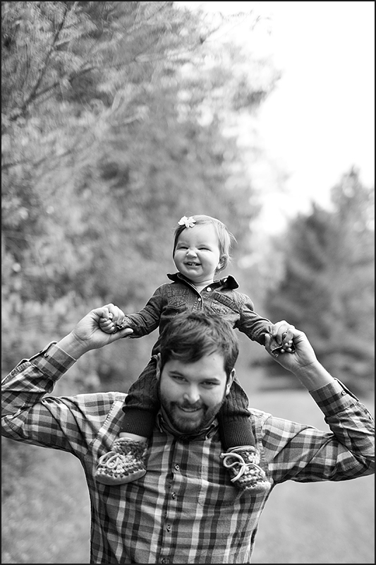 a photo of a father carrying his baby on his shoulders at a fall family session in uxbridge ontario