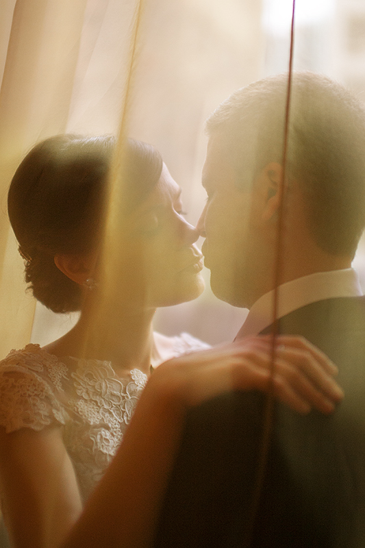a photo of a bride and groom cuddling under a curtain at a wedding at the rosewater toronto