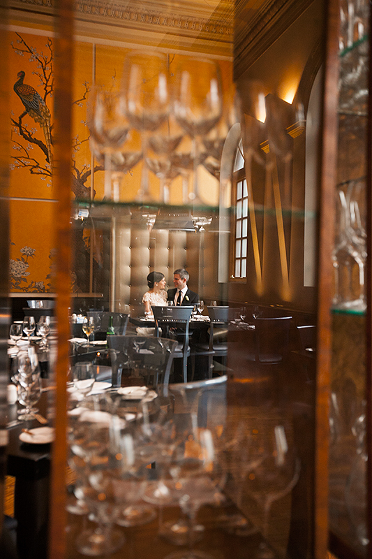 a photo of a bride and groom sitting through glass at a wedding at the rosewater toronto