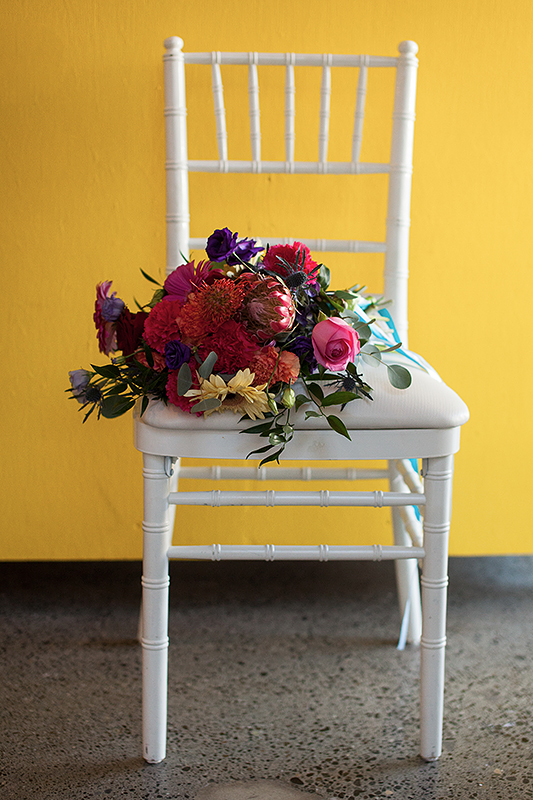 a photo of the flowers on a white chair at a frida inspiration wedding in vancouver
