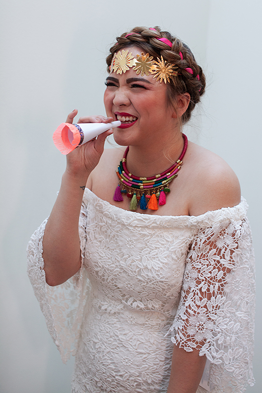 a bridal portrait blowing noise makers at a frida inspiration wedding in vancouver