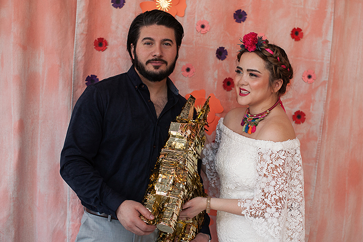 a photo of a bride and groom holding a gold piñata at a frida inspiration wedding in vancouver