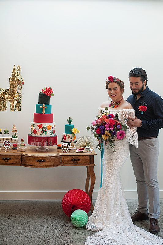 a photo of a bride and groom laughing at the cake table at a frida inspiration wedding in vancouver
