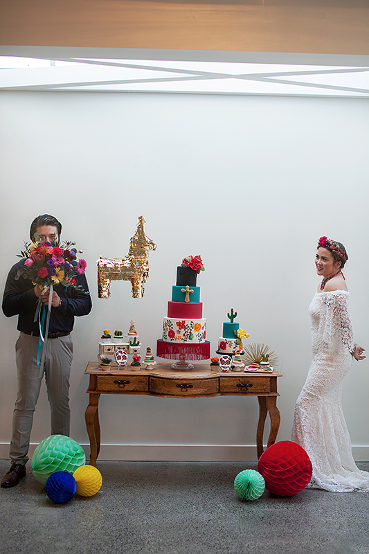 a photo of a bride and groom playing with flowers at the cake table at a frida inspiration wedding in vancouver