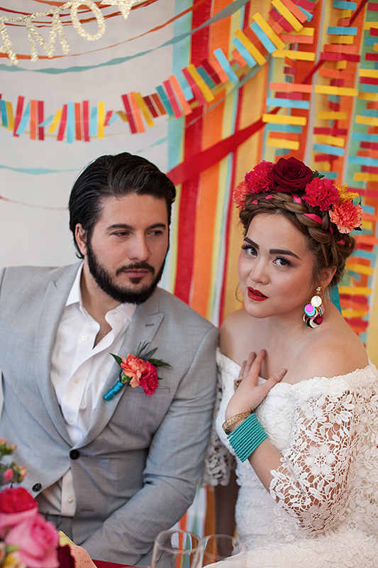 a photo of a bride and groom sitting at a table with a colourful backdrop at a frida inspiration wedding in vancouver