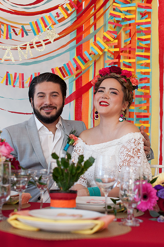 a photo of a bride and groom sitting at a table laughing with a colourful backdrop at a frida inspiration wedding in vancouver