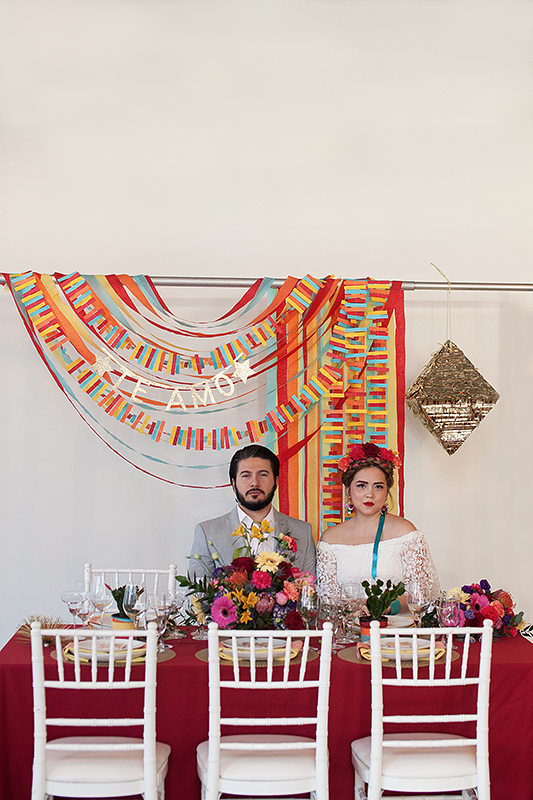 a photo of a bride and groom sitting at a table with a colourful backdrop te amo at a frida inspiration wedding in vancouver