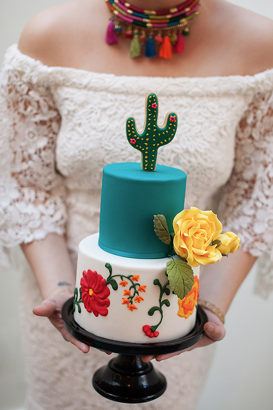 a photo of the bride holding the cake at a frida inspiration wedding in vancouver