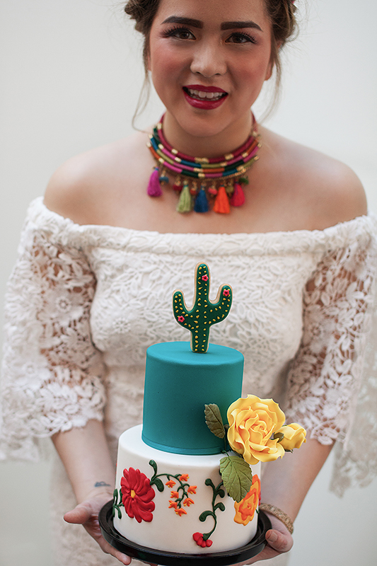 a photo of the happy bride holding the cake at a frida inspiration wedding in vancouver