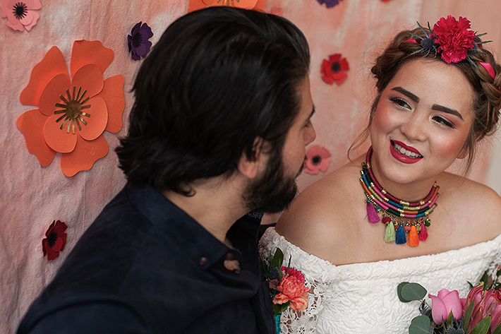 a photo of a bride and groom against floral backdrop at a frida inspiration wedding in vancouver