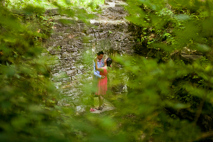 a photo of a couple standing in a doorway of an old mill with greenery at a summer engagement in balls falls ontario