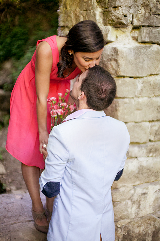 a photo of a couple kissing in a doorway of an old mill holding flowers at a summer engagement in balls falls ontario