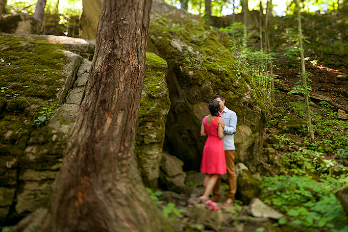 a photo of a couple kissing in front of a unique rock formation at a summer engagement in balls falls ontario