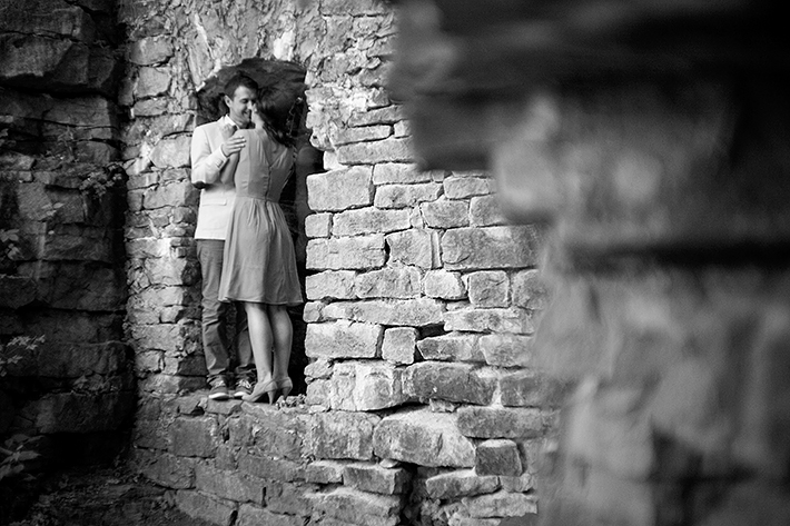 a photo of a couple standing in a doorway laughing at the old mill at a summer engagement in balls falls ontario