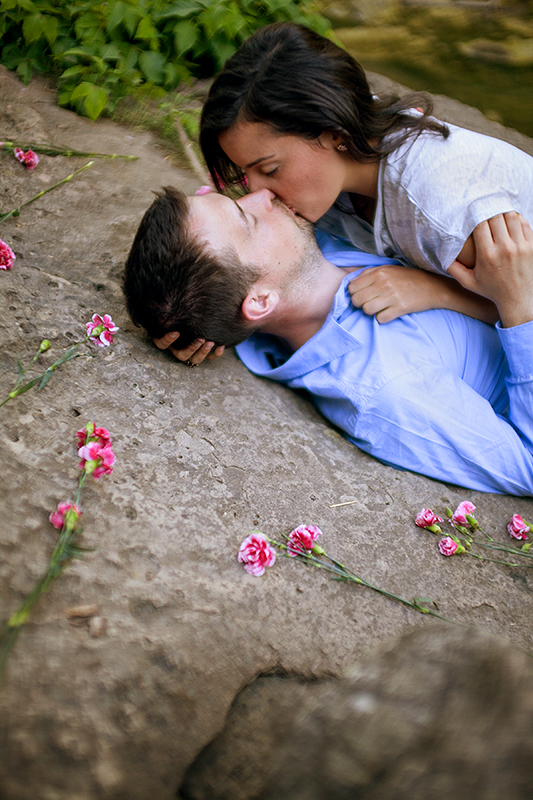 a photo of a couple kissing laying down on top of rocks with flowers scattered at a summer engagement in balls falls ontario