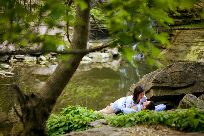 a photo of a couple laying down in front of rocks and a stream at a summer engagement in balls falls ontario