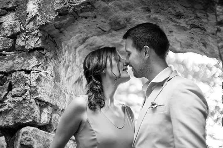a photo of a couple snuggling in a doorway of an old mill at a summer engagement in balls falls ontario