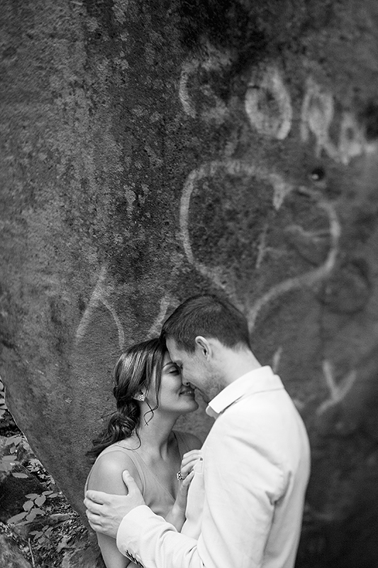 a photo of a couple snuggling in front of a heart graffiti rock at a summer engagement in balls falls ontario
