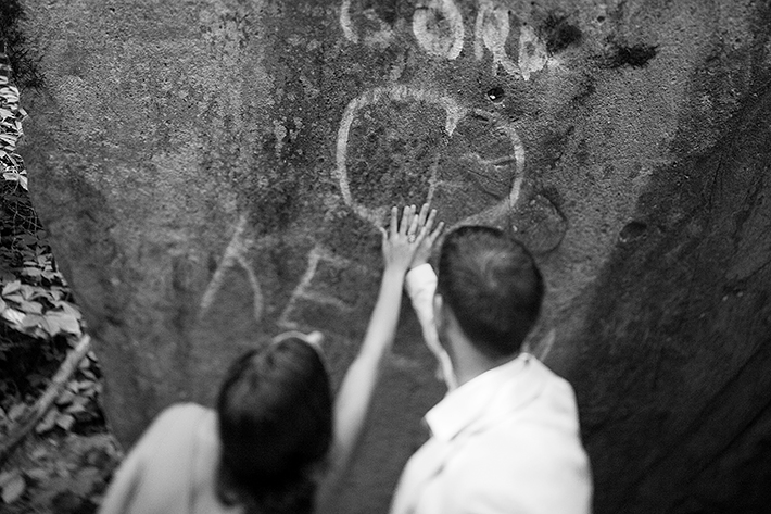 a photo of the couple's rings in front of a heart graffiti rock at a summer engagement in balls falls ontario