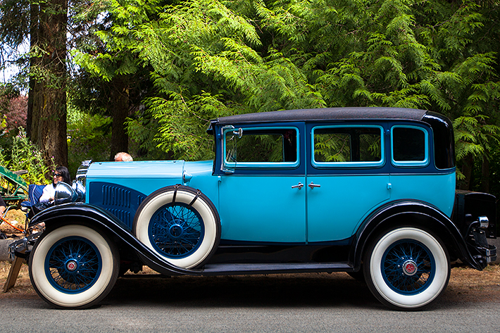 a travel photo of a blue car at the antique car show at saanich museum in sidney british columbia