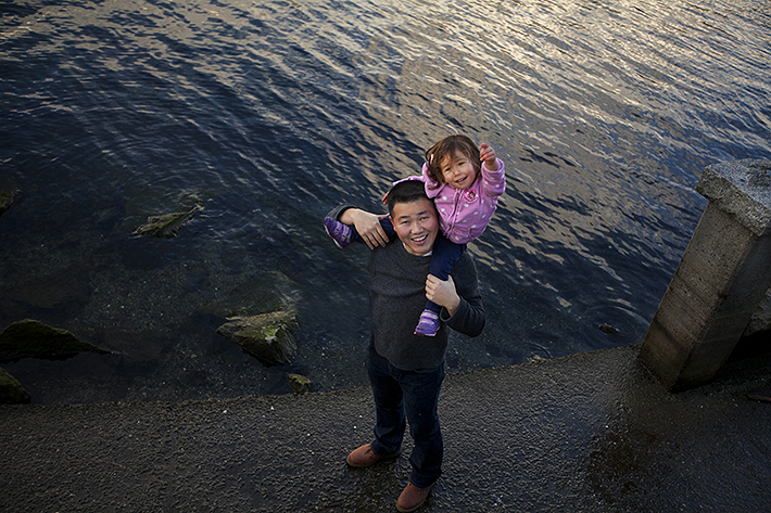a family photo of a daughter being carried on her fathers back at the harbour front in port moody, bc
