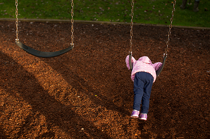 a family photo of a daughter playing on the swings in port moody, bc