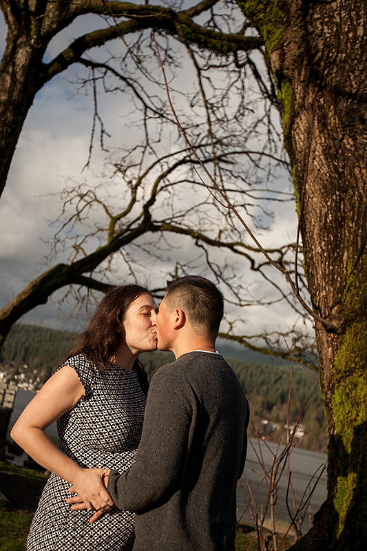 a family photo of the parents kissing in port moody, bc